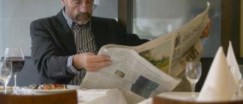 homme lisant son journal avec un verre de vin